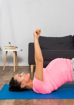 Vista laterale della donna incinta che si esercita sulla stuoia a casa