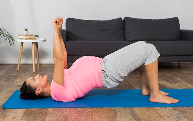 Side view of pregnant woman on exercising mat lifting arms up