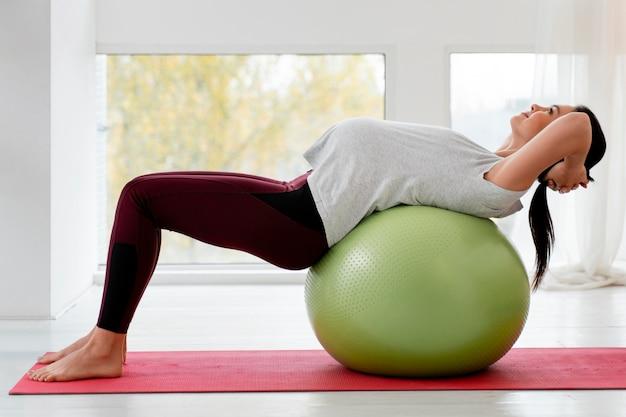 フィットネスボールで運動している妊婦の側面図