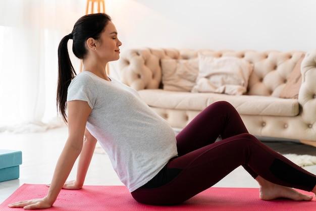 フィットネスマットで運動している妊婦の側面図
