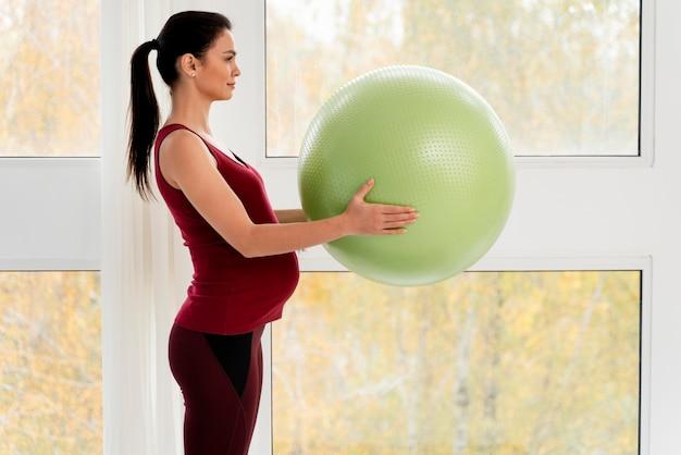 녹색 피트 니스 공을 들고 측면보기 임신 한 여자
