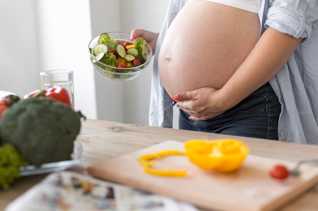 Side view pregnant woman holding a salad