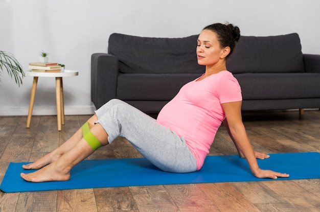 Side view of pregnant woman at home exercising with elastic band