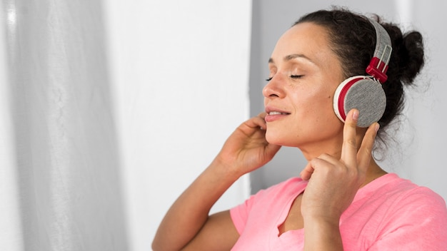 Side view of pregnant woman at home listening to music on headphones
