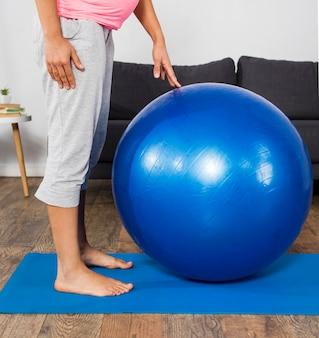 Vista laterale della donna incinta a casa con palla e tappetino per esercizi