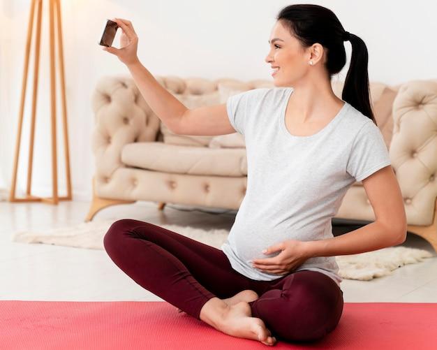 Vista laterale della donna incinta nella posizione del loto prendendo un selfie