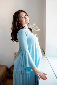 Side view pregnant woman posing in blue dress