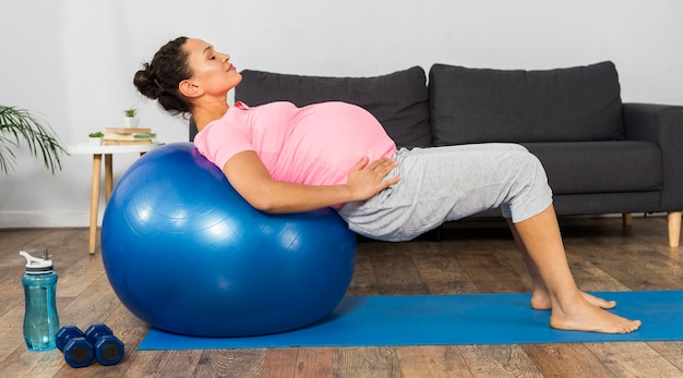 Side view of pregnant woman using ball to exercise