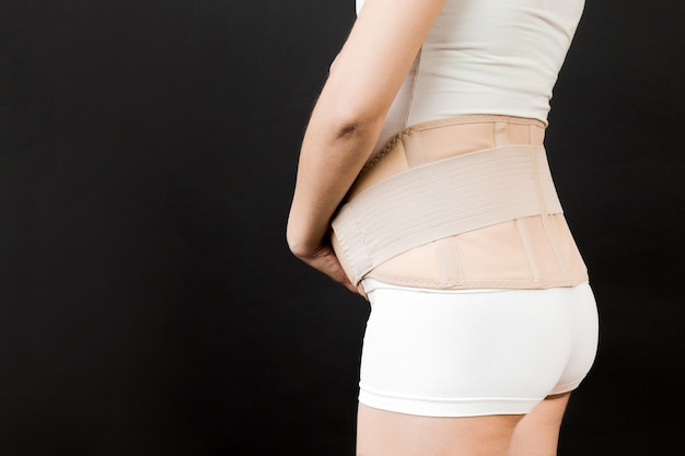 Side view of pregnant woman wearing pregnancy belt at black background with copy space. close up of orthopedic abdominal support belt concept.