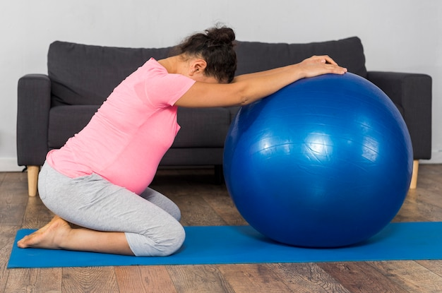 Side view of pregnant woman with ball and exercise mat at home