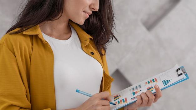 Vista laterale della donna incinta che lavora da casa con appunti e penna