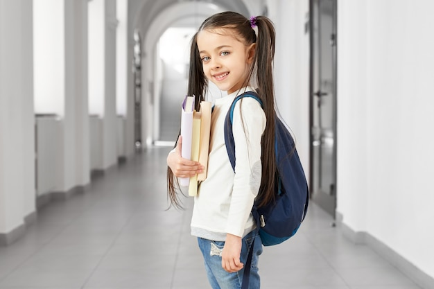 Side view of pretty and cute school girl with funny hairstyle holding notes posing at corridor of luxury school.