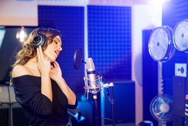 Side view of a pretty woman standing in studio with headphones and singing in front of the microphone.