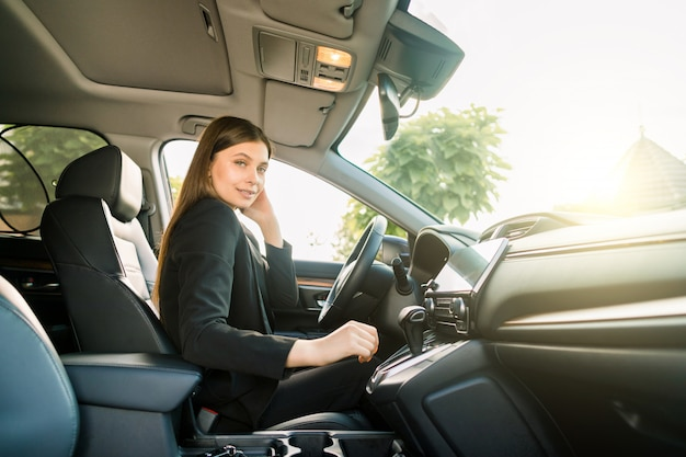 Side view of pretty young lady businesswoman sitting in drivers seat in her car, smiling