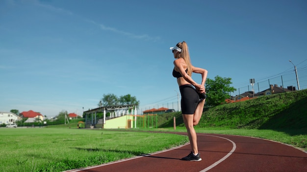 Side view of pretty young woman wearing black outfit and cap practicing relaxing exercises, increasing quadriceps flexibility. fit girl stretching legs before training at stadium in summer sunny day.