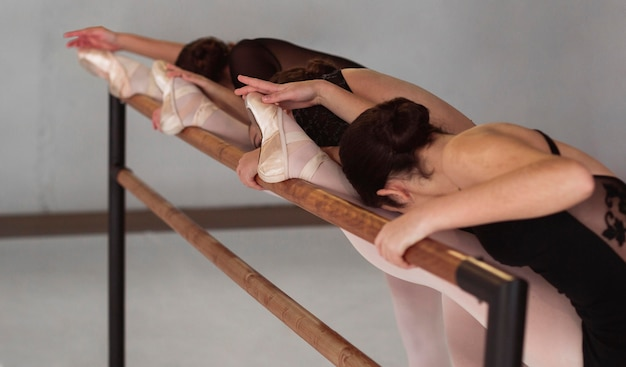 Side view of professional ballerinas training while wearing pointe shoes