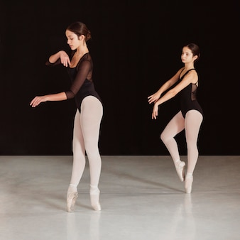 Side view of professional ballet dancers practicing together in pointe shoes