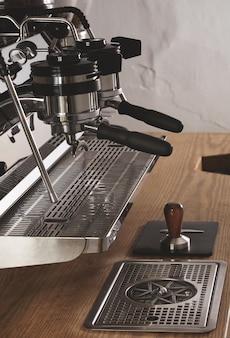 Вид сбоку профессиональная хромированная кофемашина с двумя головками и заряженными портафильтрами в кафе-магазине на деревянном толстом столе и тампер на кожаном падеспрессо, капучино, латте.