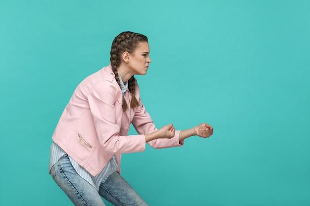 분홍색 재킷이 서서 당기는 제스처나 권투 주먹을 보여주는 캐주얼 스타일의 젊은 진지한 화난 소녀의 측면 프로필 초상화. 실내 스튜디오 촬영에 고립 된 녹색 배경입니다.