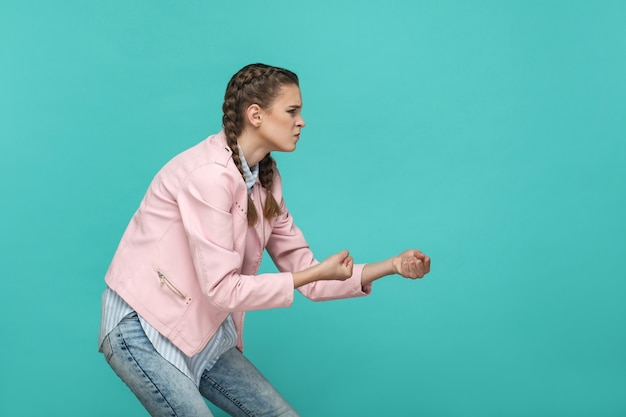 Side view profile of serious angry girl with pink jacket standing and showing pulling gesture