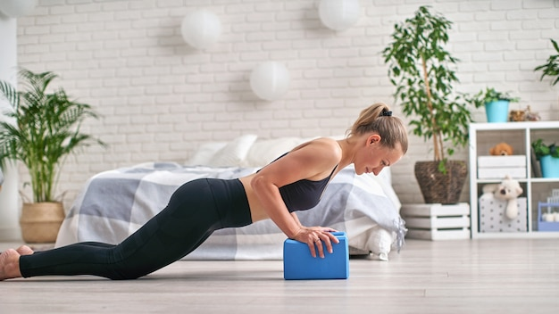 Side view profile of well-shaped athlete. she is staying in plank and using yoga blocks for wrists.