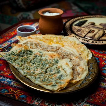 Side view qutab assorted with sumac and yogurt in tray