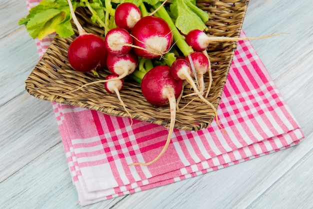Side view of radishes in basket plate on plaid cloth and wooden background