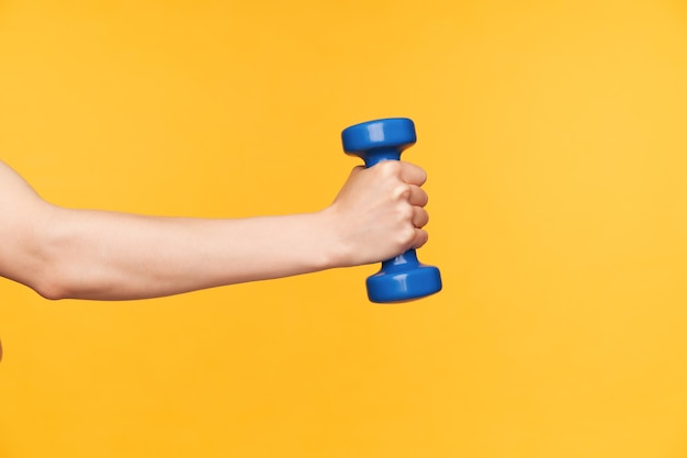 Side view of raised female hand with blue dumbbell exercising biceps while being isolated over yellow background. body care and fitness concept Free Photo