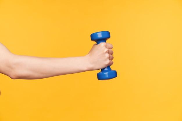 Vista laterale della mano femminile sollevata con il manubrio blu che esercita il bicipite mentre è isolato sopra priorità bassa gialla. la cura del corpo e il concetto di fitness