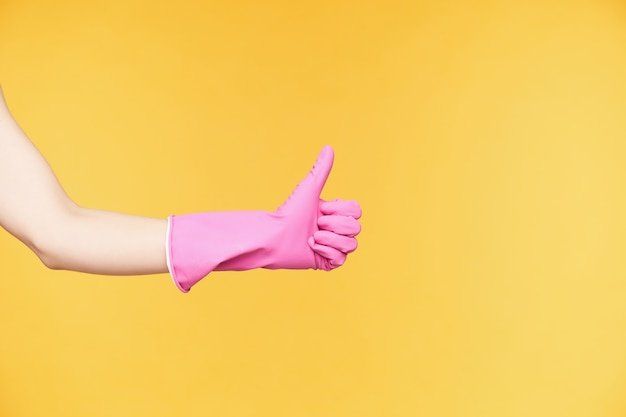 Vista laterale della mano alzata in guanti di gomma che solleva il pollice mentre mostra emozioni positive, essendo soddisfatto mentre finisci le pulizie di primavera, isolato su sfondo arancione