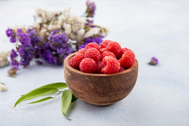 Side view of raspberries in bowl with flowers and leaves on white