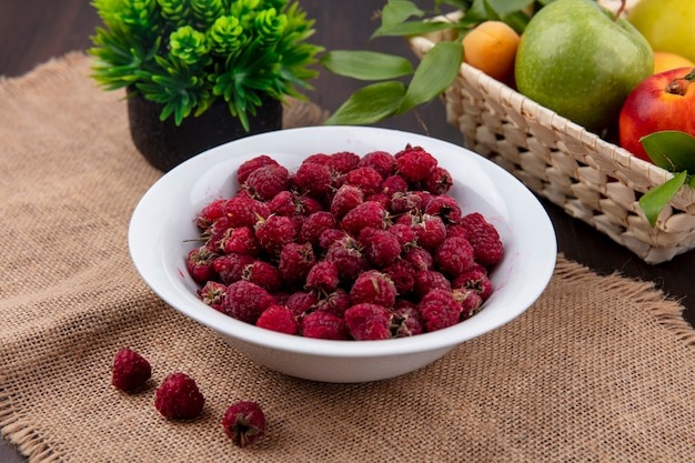 Side view of raspberries in a plate with colored apples in a basket on a beige napkin