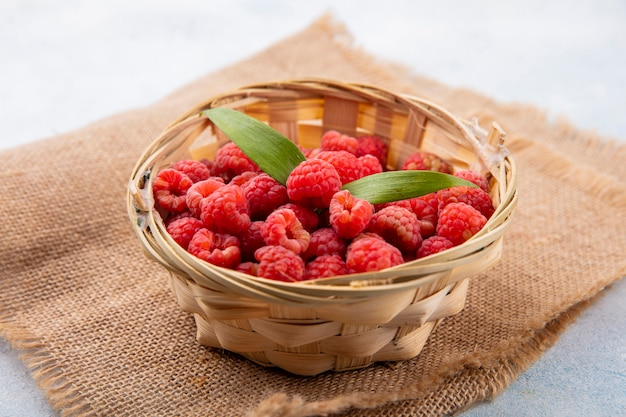 Side view of raspberries with leaves in basket on sackcloth and on white