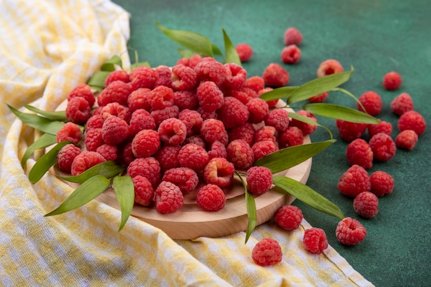 Side view of raspberries with leaves on cutting board on plaid cloth and on green