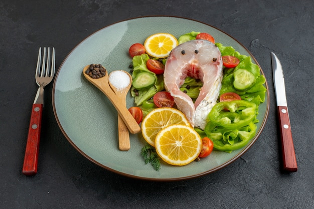 Vista laterale di pesce crudo e verdure fresche tritate fette di limone spezie su un piatto grigio e posate impostato su superficie nera in difficoltà