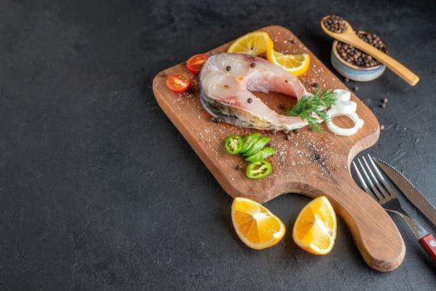 Vista laterale di pesce crudo e verdure fresche tritate fette di limone spezie su una tavola di legno posate impostato su nero superficie in difficoltà