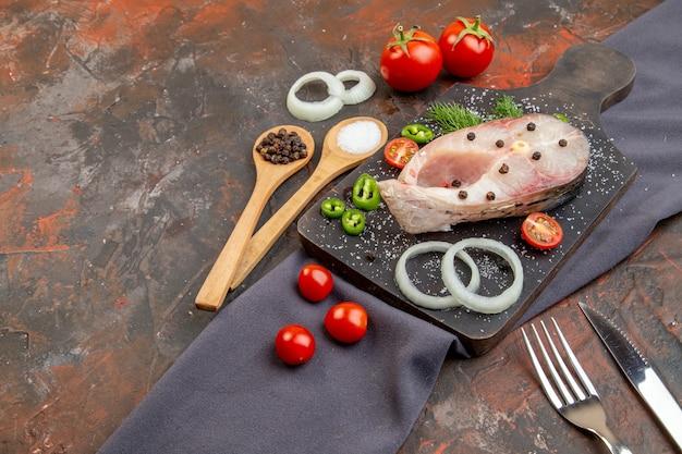 Vista laterale di pesci crudi e pomodori verdi cipolla pepe sul tagliere nero sulle posate asciugamano impostato su una superficie di colore misto