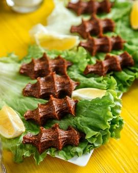 Vista laterale di un piatto di carne cruda in cucina turca cig kofte con limone su lattuga