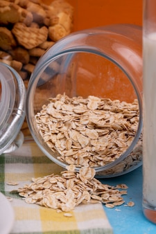 Side view of raw oatmeal flakes scattered from glass jar