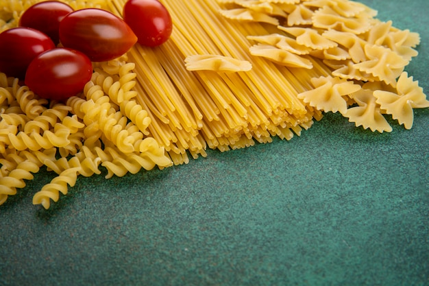 Side view of raw pasta with raw spaghetti and cherry tomatoes on a green surface