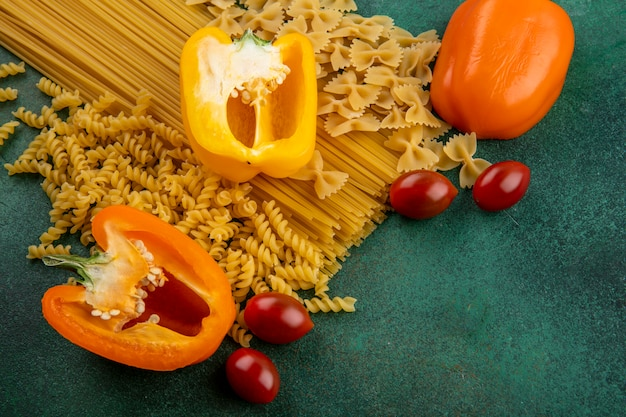 Side view of raw pasta with raw spaghetti and colored bell peppers and cherry tomatoes on a green surface