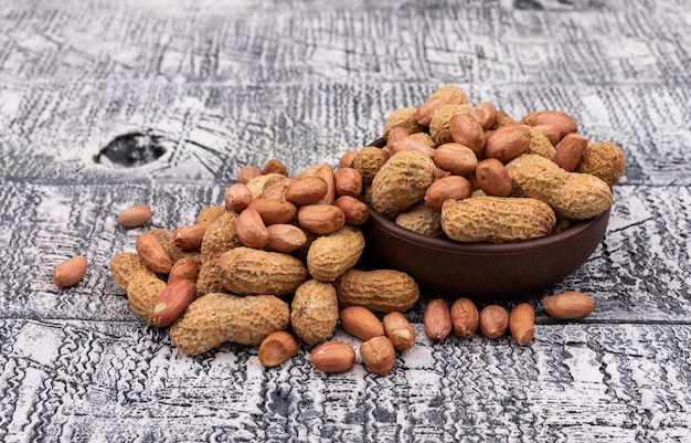 Side view raw peanuts in bowl on wooden  horizontal