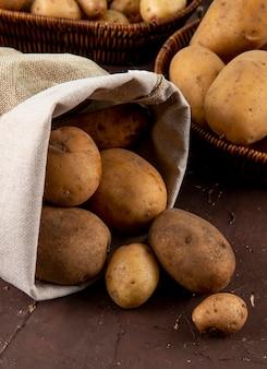 Вид сбоку сырой картофель в сумке на коричневом фоне