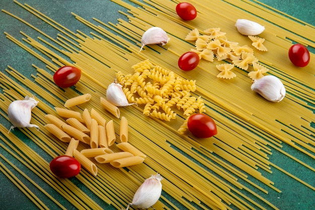 Side view of raw spaghetti with pasta cherry tomatoes and garlic on a green surface