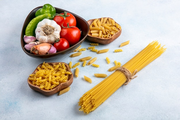 Side view of raw spaghetti with raw pasta in bowls with garlic and tomatoes in a bowl on a gray surface