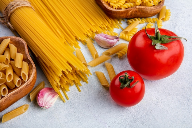 Side view of raw spaghetti with raw pasta in bowls with garlic and tomatoes on a gray surface