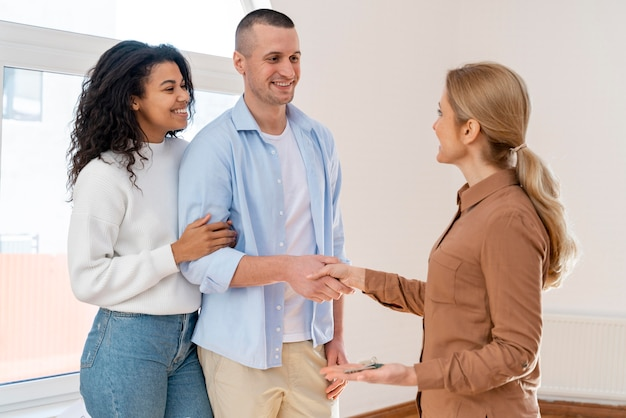 Side view of realtor shaking hands with couple for new house