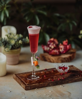 Side view of red alcohol cocktail with pomegranate beans on a wooden board on the table