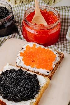 Вид сбоку тост с красной и черной икрой и белым хлебом с творогом, красной икрой и черной икрой на доске