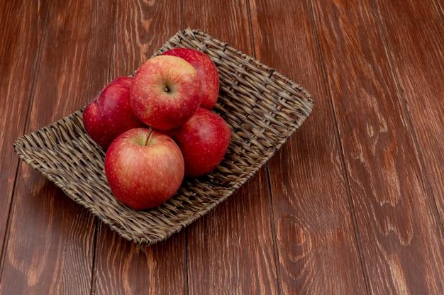Vista laterale del piatto rosso della merce nel carrello delle mele su superficie di legno con lo spazio della copia